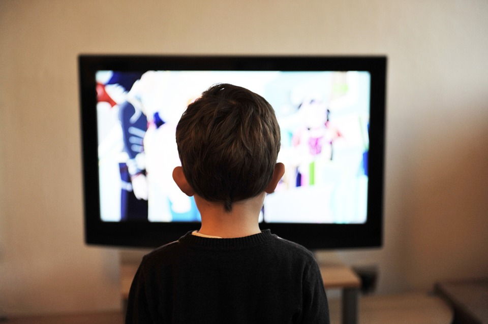A kid is watching TV